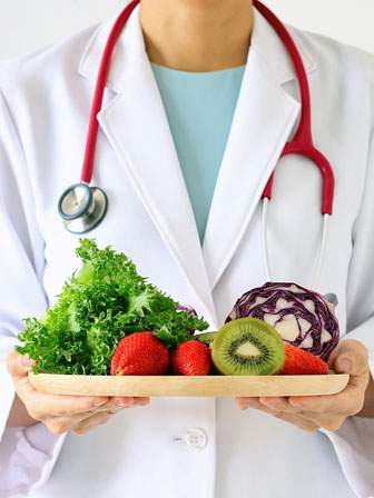 doctor holding a tray of fresh fruits and vegetables